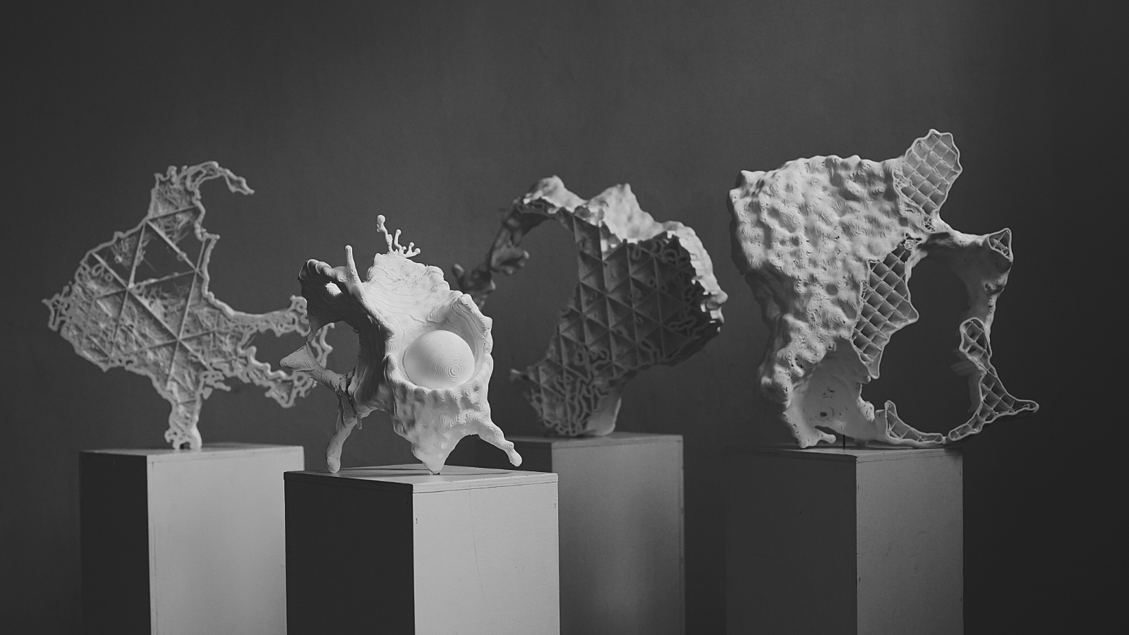 A selection of 3D-printed shapes on pedestals, resembling natural patterns mixed with geometric designs.